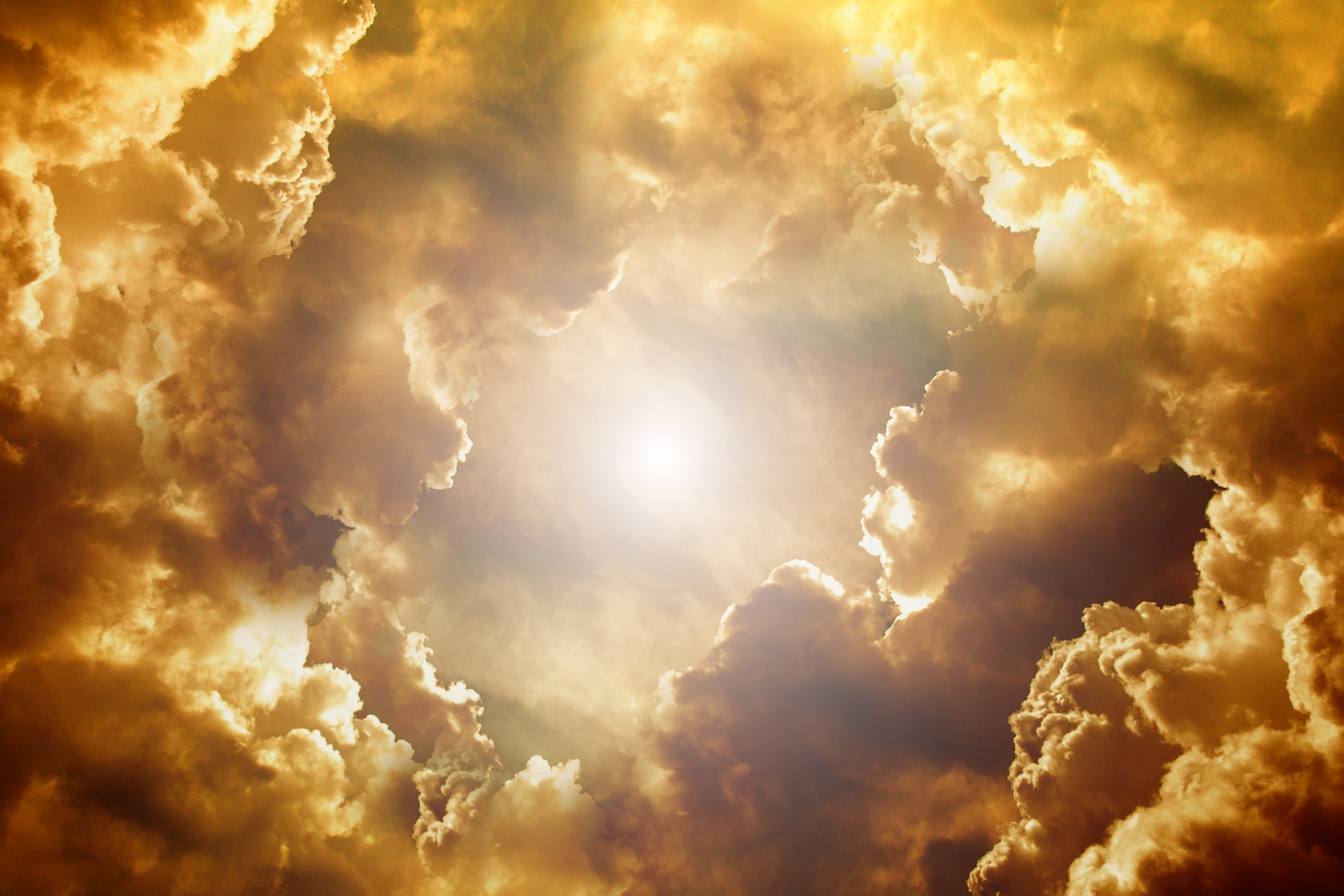The sun shining through golden tinted clouds