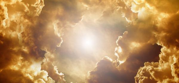 The sun shining through golden tinted clouds